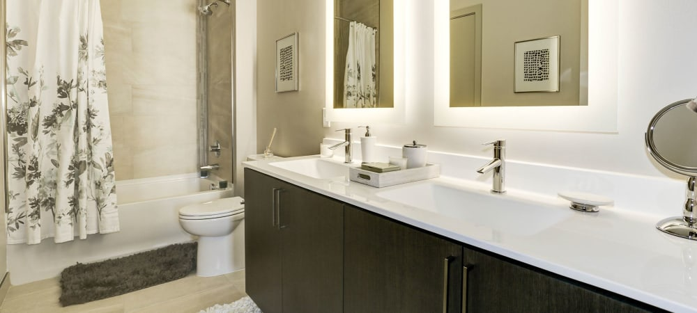 Spacious bathroom with large mirror and ample counter space at Metropolitan Rockville Town Center in Rockville, Maryland
