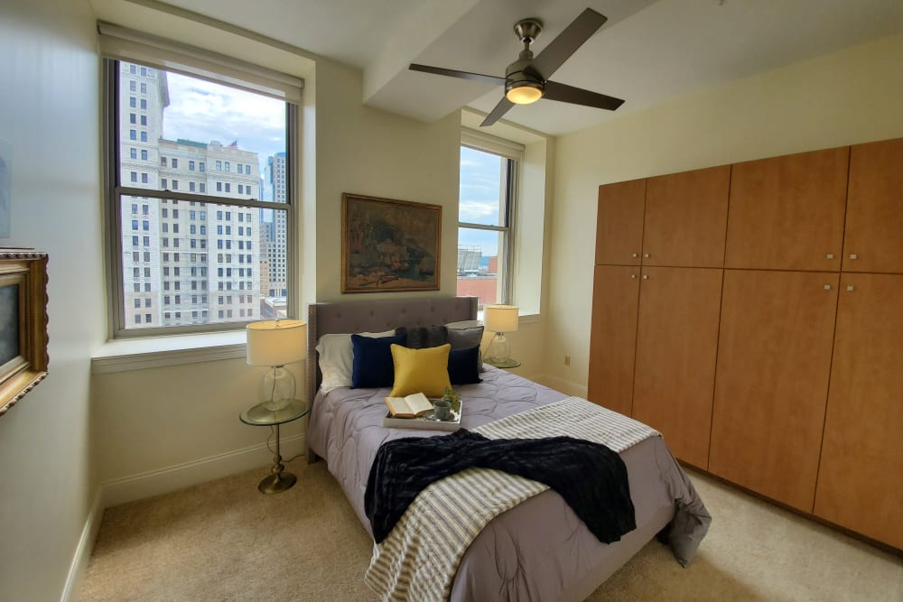 Spacious bedroom at The Reserve at 4th and Race in Cincinnati, Ohio with ceiling fan and ample natural light from large windows