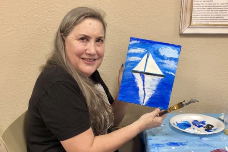Resident showing off her work in an art class at Casa Del Rio Senior Living in Peoria, Arizona