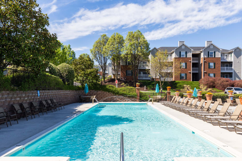 Resort-style swimming pool with plenty of lounge chairs at Glade Creek Apartments in Roanoke, Virginia
