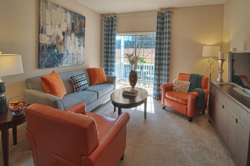 Living room with private balcony at Amber Chase Apartment Homes in McDonough, Georgia