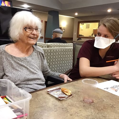 Resident playing games with a masked caretaker at Glen Carr House Memory Care in Derby, Kansas