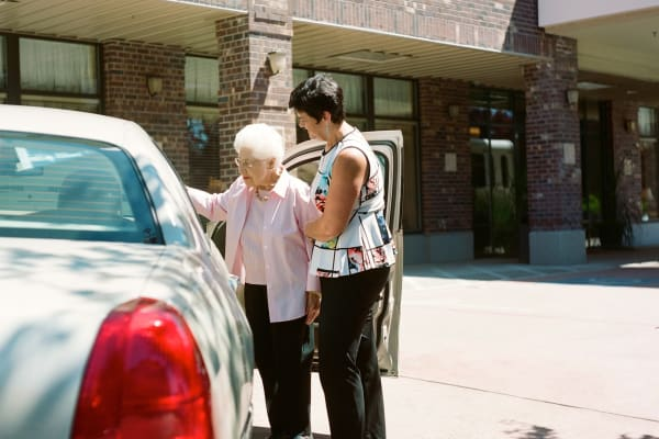 A staff member helping a resident into a car at Merrill Gardens.