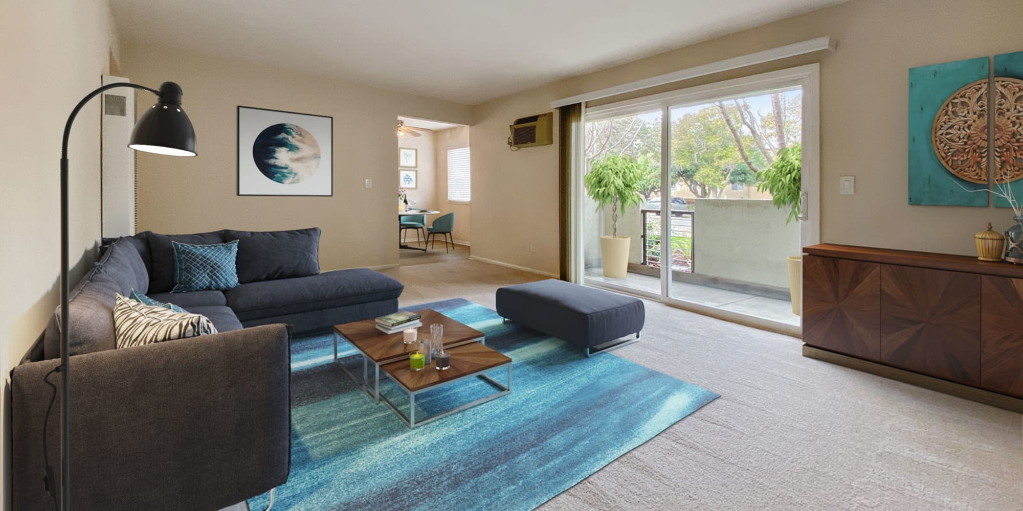 Plush carpeting and modern furnishings in a model home's living area at Pleasanton Place Apartment Homes in Pleasanton, California
