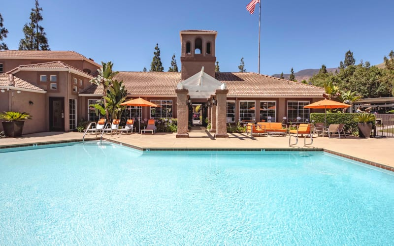 Large swimming pool with lounge chairs and umbrellas at Sierra Del Oro Apartments in Corona, California
