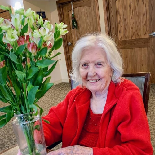 A resident with a large bouquet of flowers at Glen Carr House Memory Care in Derby, Kansas