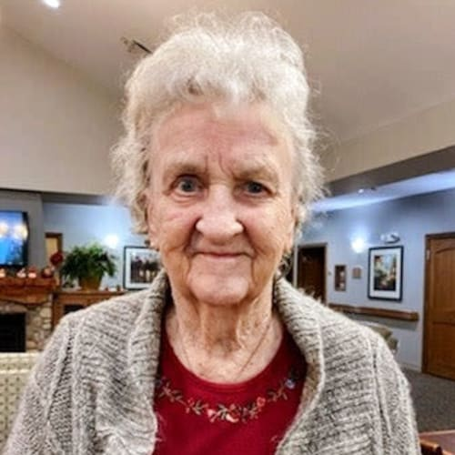 A resident smiling in a lounge at Glen Carr House Memory Care in Derby, Kansas