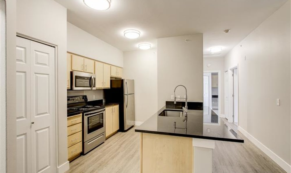 Kitchen and hallway in a unit at River Trail Apartments in Puyallup, Washington