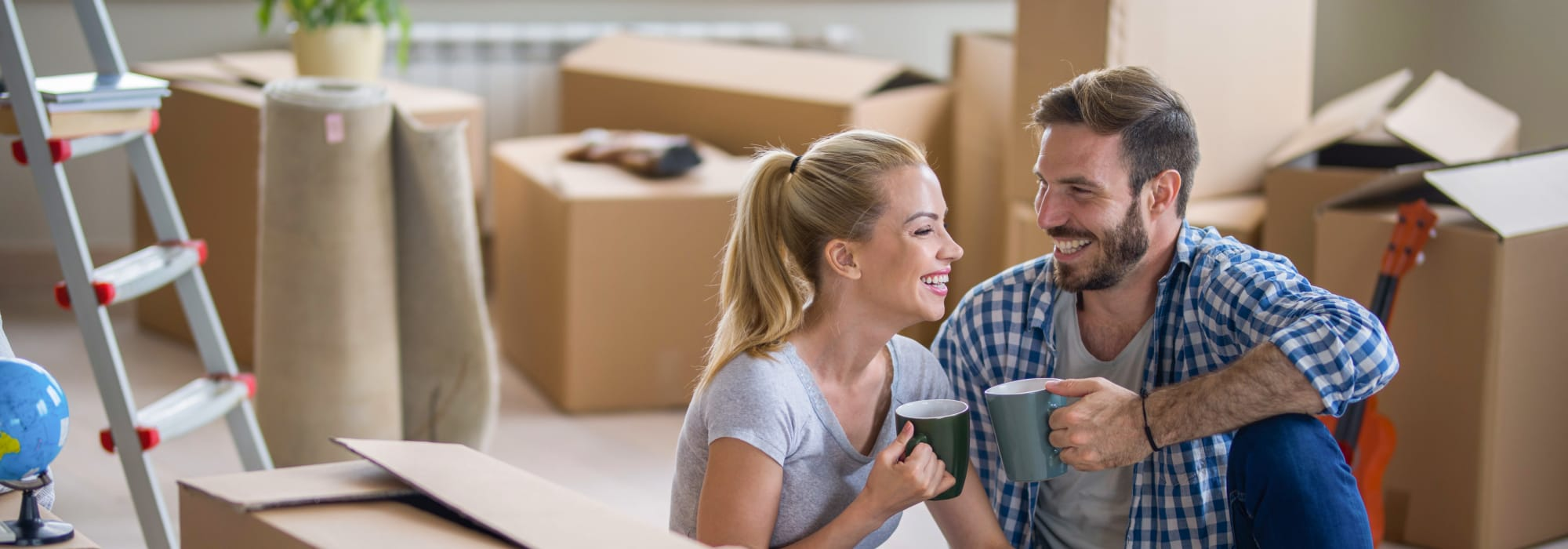 Couple Smiling Amidst Moving Boxes