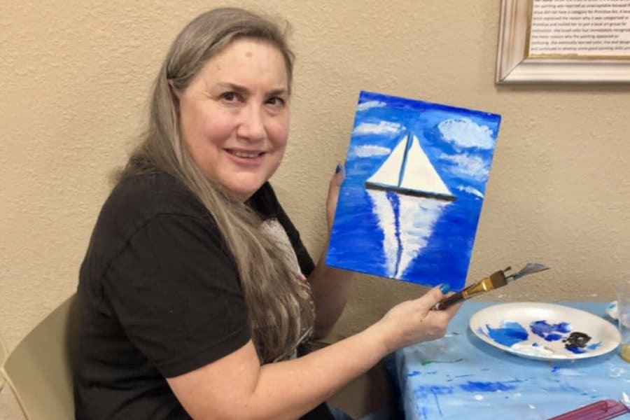 Resident showing off her painting in an art class at Bella Vista Senior Living in Mesa, Arizona