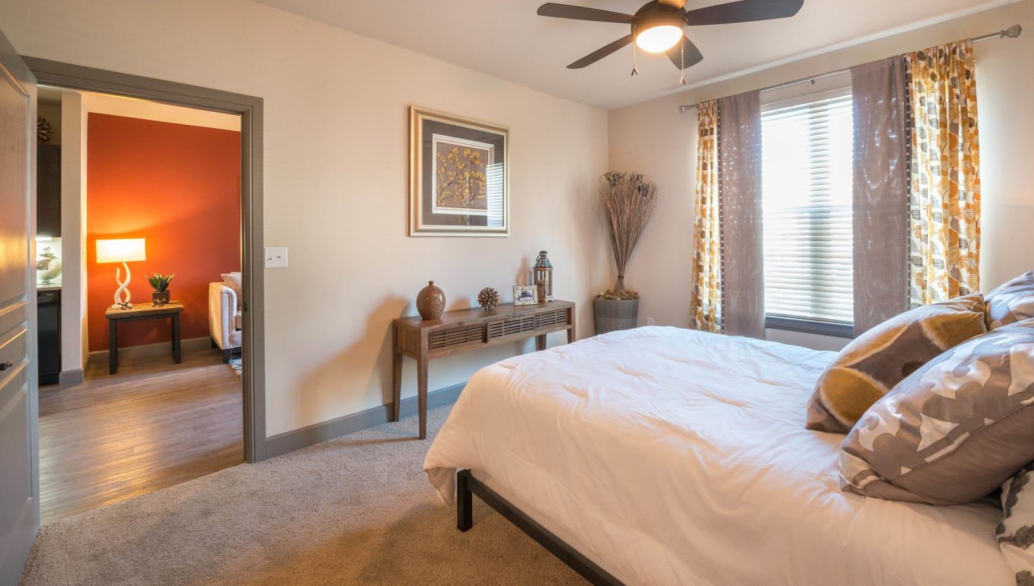 Ceiling fan and draped windows in a model home's bedroom at Union At Carrollton Square in Carrollton, Texas