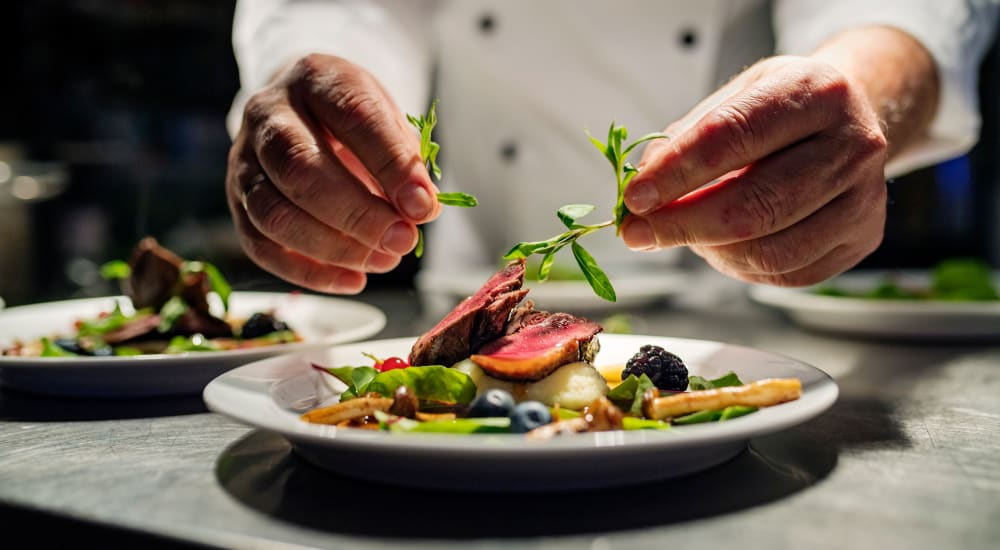A chef topping a dish with garnish at The Springs at Lake Oswego in Lake Oswego, Oregon