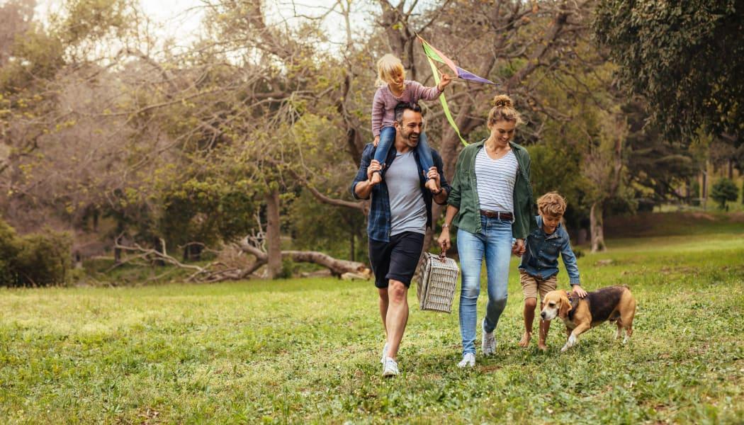 Family walking their dog in Waco, Texas near Tuscany Ranch