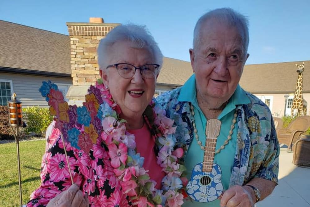 A cute couple in Hawaiian shirts and leis at Villas of Holly Brook Shelbyville in Shelbyville, Illinois