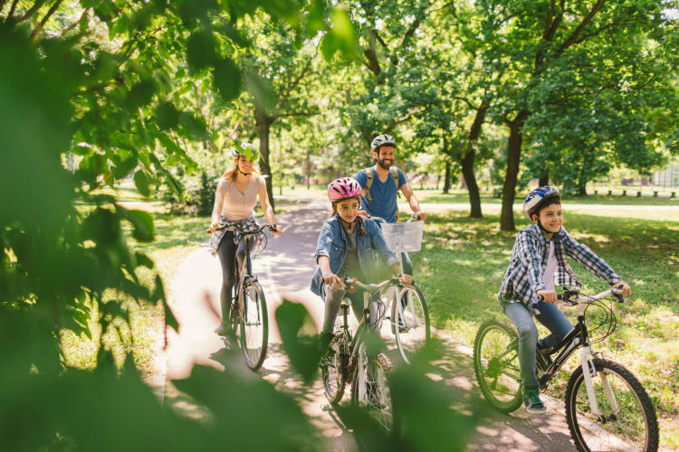 Family riding bikes through a park near Merrimack, New Hampshire near London Court Apartments