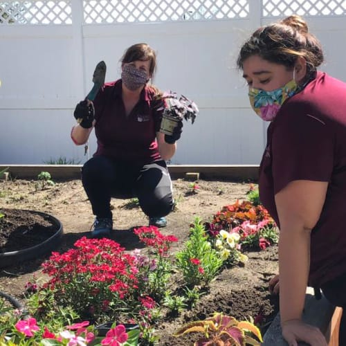 Two team members gardening at Oxford Glen Memory Care at Owasso in Owasso, Oklahoma