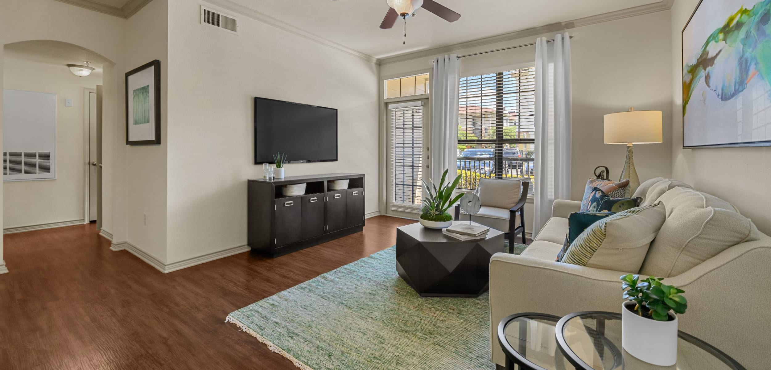 Open and bright living area with wood style flooring and ceiling fan at Marquis Lakeline Station in Austin, Texas