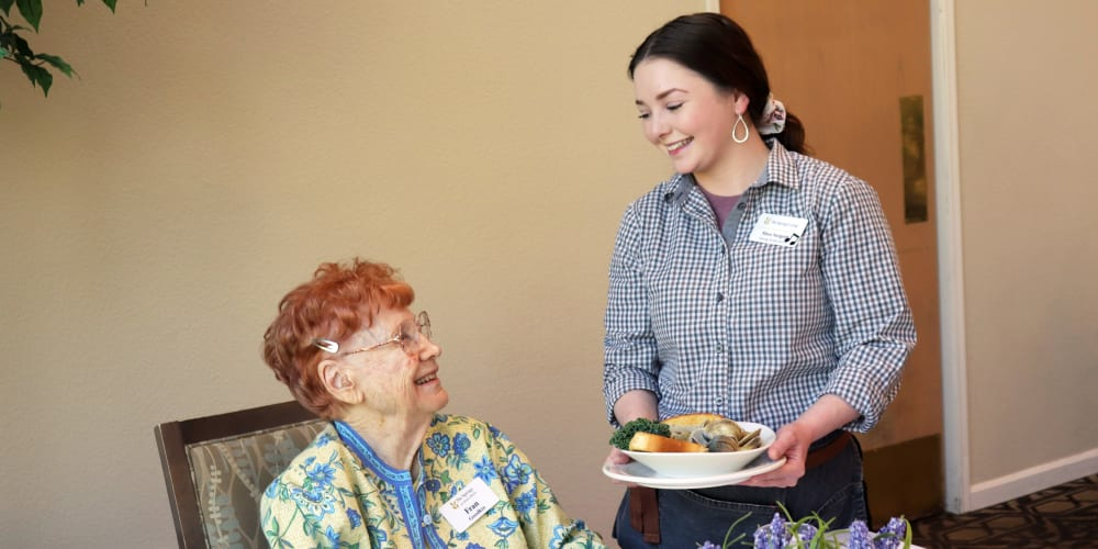 Resident being served dinner in dining room at The Springs at Anna Maria in Medford, Oregon