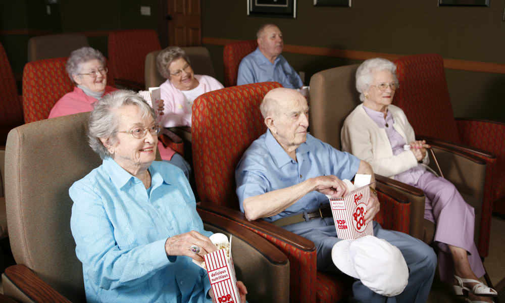 Resident watching a movie in the theater at Deer Crest Senior Living in Red Wing, Minnesota