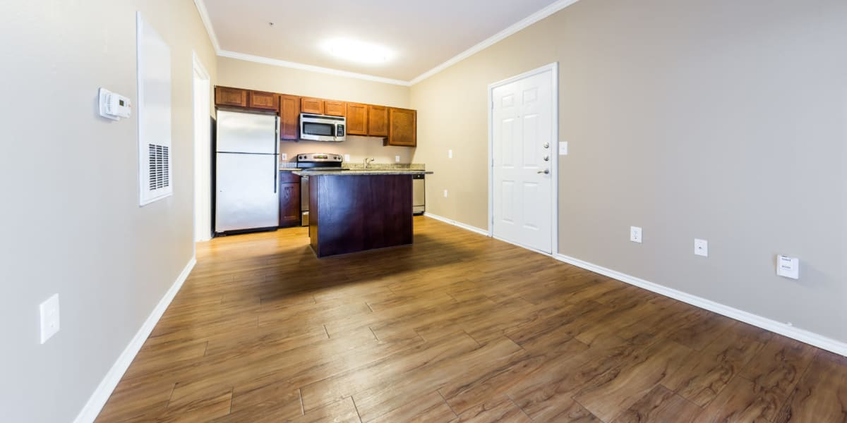 Open living space with kitchen island and wood flooring at Marquis at Barton Trails in Austin, Texas