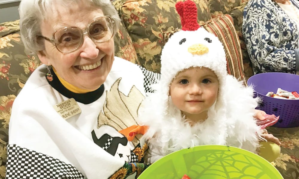 A resident with a child dressed as a chicken on Halloween at Meadowlark Estates Gracious Retirement Living in Lawrence, Kansas