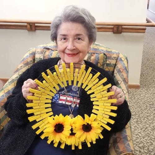 Resident holding a sunflower-themed wreath at Creekside Village in Ponca City, Oklahoma