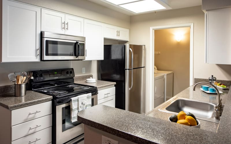Renovated kitchen with white cabinets at Sierra Del Oro Apartments in Corona, California