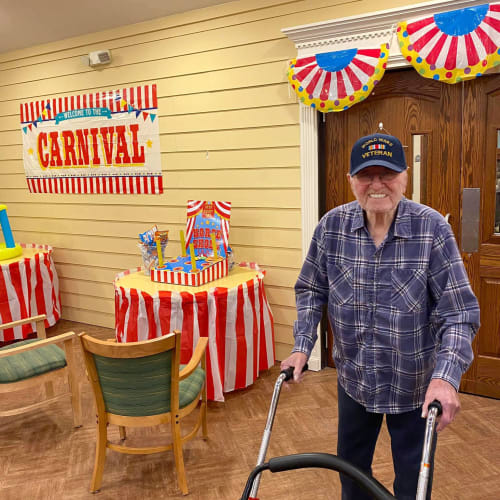 A resident walking into a carnival event at Oxford Glen Memory Care at Carrollton in Carrollton, Texas