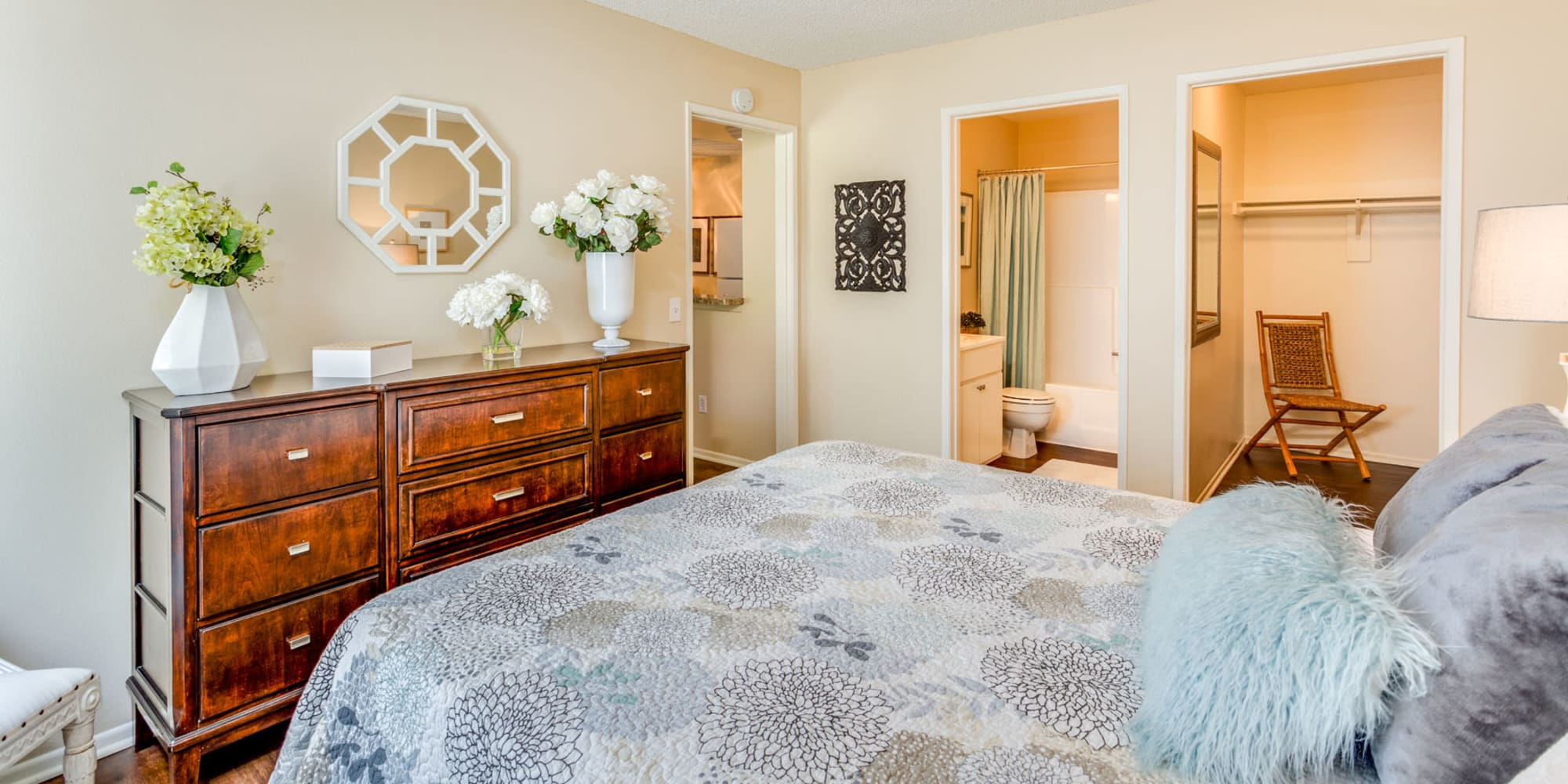 Classically furnished model home's primary bedroom with an en suite bathroom and walk-in closet at Mountain Vista in Victorville, California