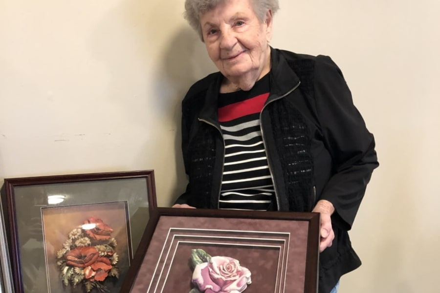 Resident showcasing her work at the show and tell crafts event at Bella Vista Senior Living in Mesa, Arizona