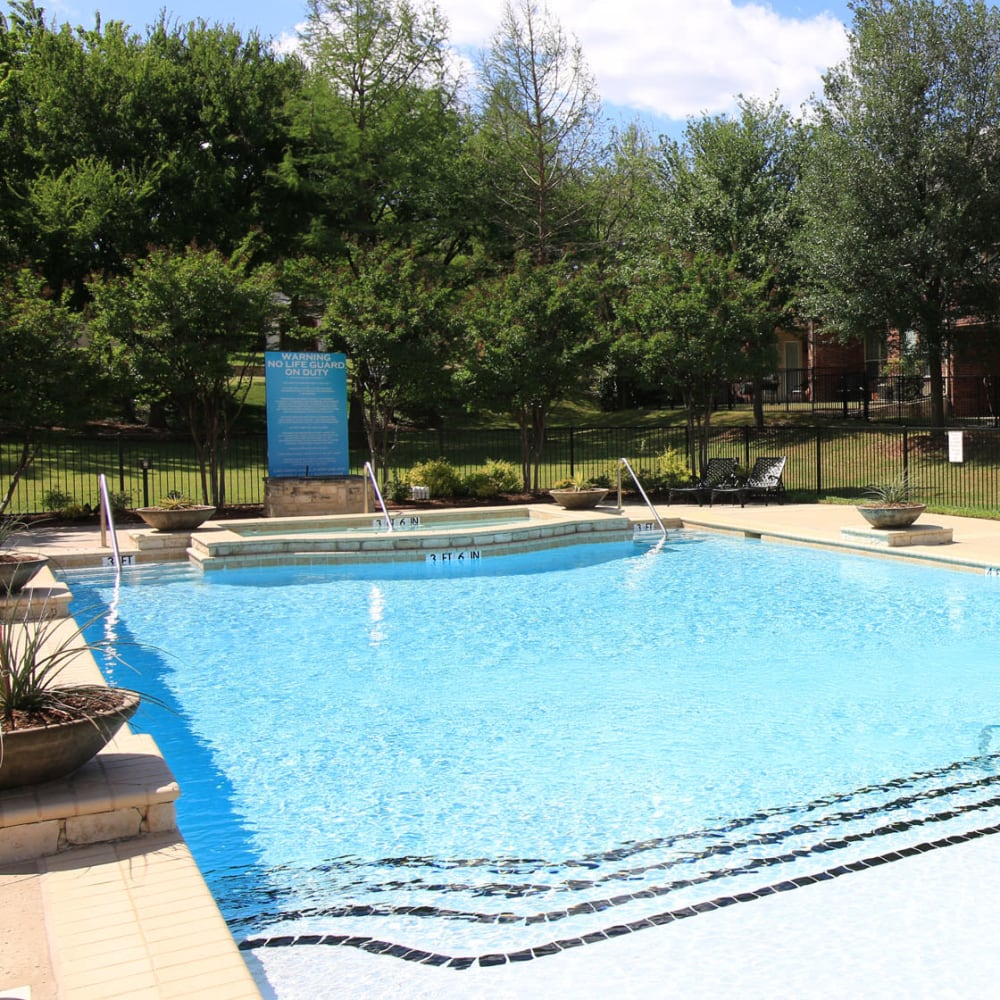 Swimming pool surrounded by mature trees at Oaks Estates of Coppell in Coppell, Texas