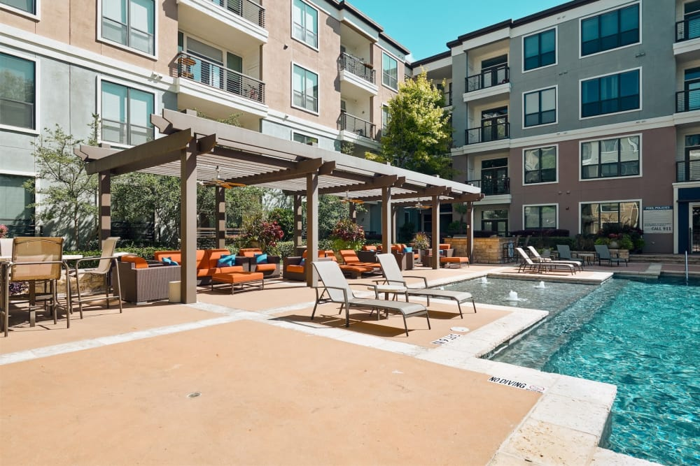 Lovely pool with tons of covered lounge area for residents to relax at Seville Uptown in Dallas, Texas