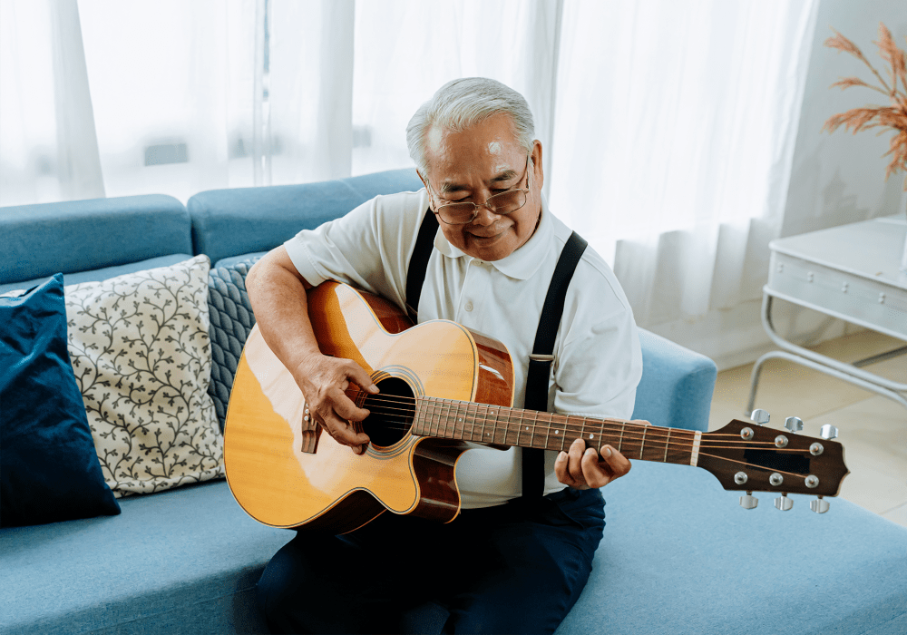 Resident sitting on a couch and playing an acoustic guitar at Hanover Place in Tinley Park, Illinois