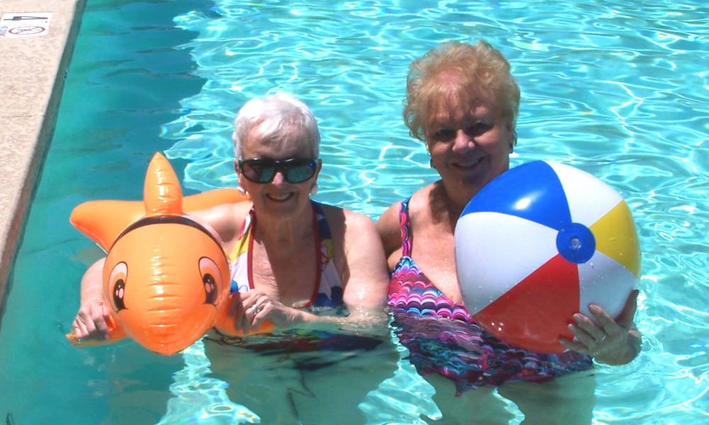 Two residents in the pool with pool toys at Steeplechase Retirement Residence in Oxford, Florida