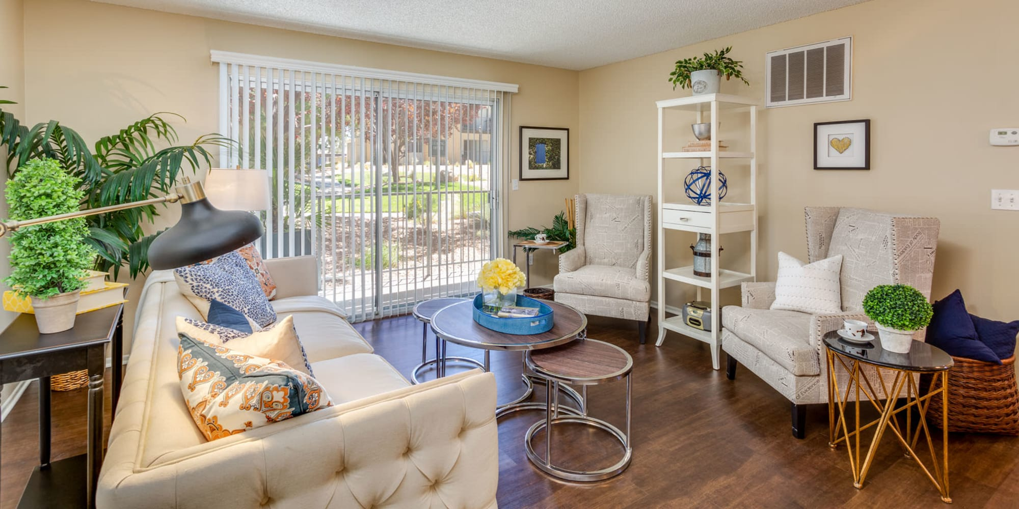 Comfortably furnished living area with hardwood flooring in a model home at Mountain Vista in Victorville, California