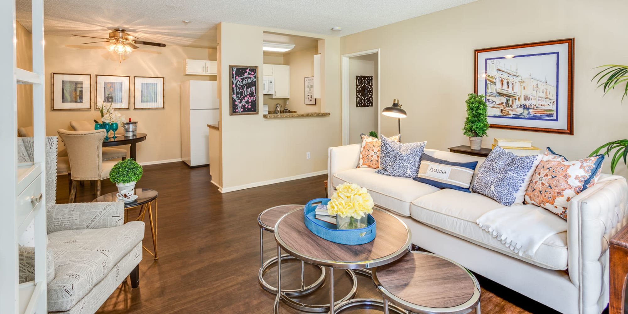 Well-furnished living area with hardwood floors in a model apartment at Mountain Vista in Victorville, California