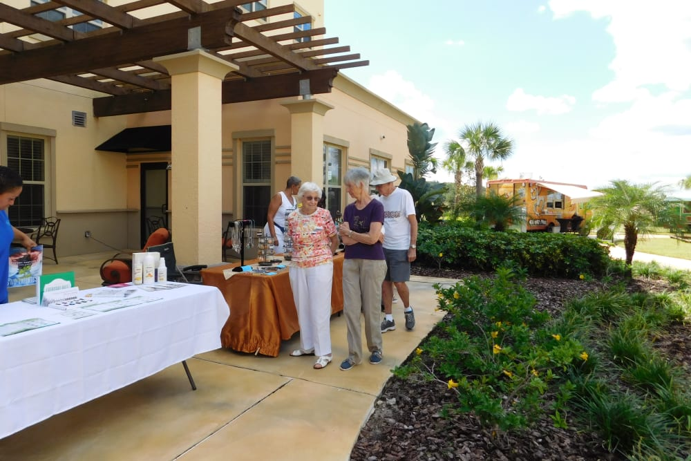 residents gathering for an outdoor event at Merrill Gardens at Solivita Marketplace in Kissimmee, Florida.