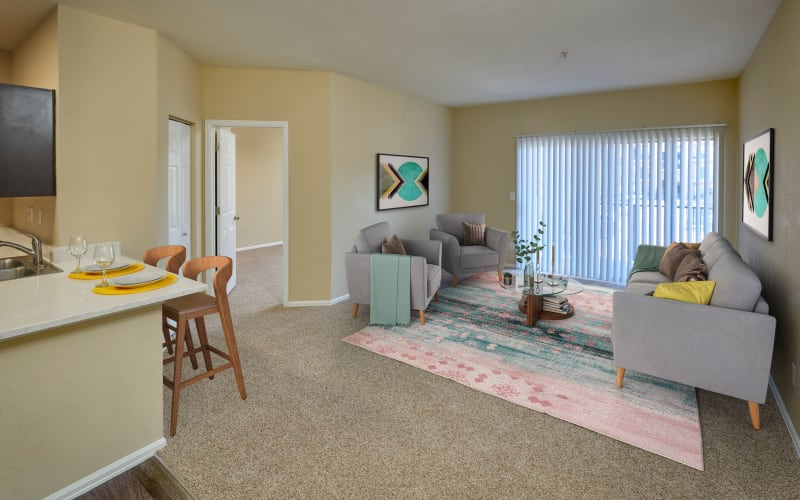 Living room with a private patio at The Crossings at Bear Creek Apartments in Lakewood, Colorado