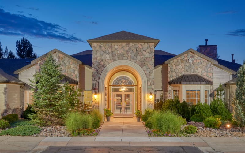 Exterior clubhouse view with beautiful landscaping at sunrise at Legend Oaks Apartments in Aurora, Colorado