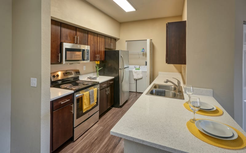 A renovated kitchen with espresso cabinets at The Crossings at Bear Creek Apartments in Lakewood, Colorado