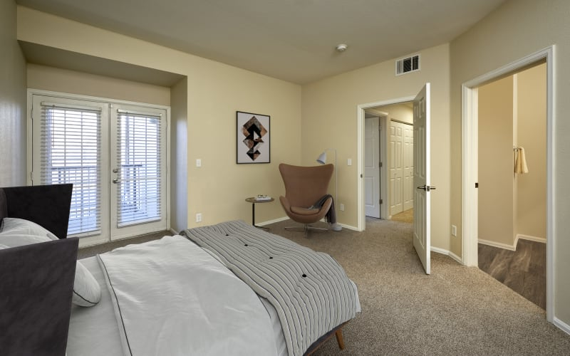 Spacious master bedroom with plush carpeting at The Crossings at Bear Creek Apartments in Lakewood, Colorado
