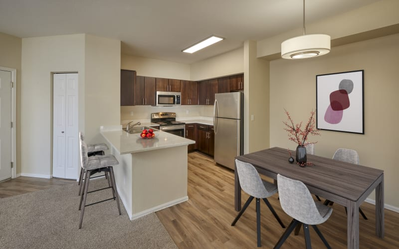 Renovated kitchen with brown cabinets at The Crossings at Bear Creek Apartments in Lakewood, Colorado