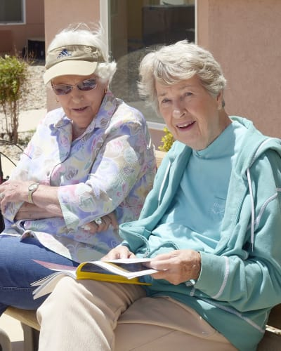 Two residents from Seasons reading outside in the sun