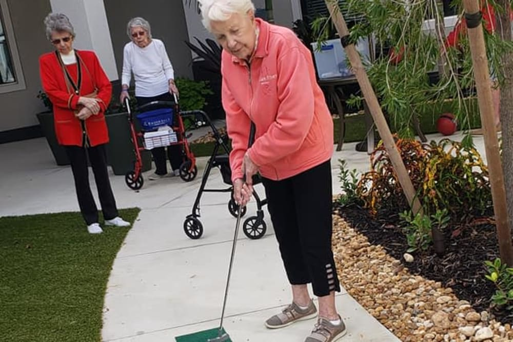 A resident playing mini golf at Atrium at Liberty Park in Cape Coral, Florida