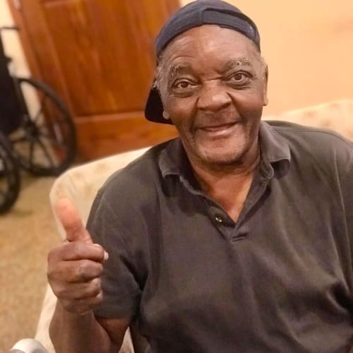 seated resident smiling and giving a thumbs up at Oxford Glen Memory Care at Carrollton in Carrollton, Texas