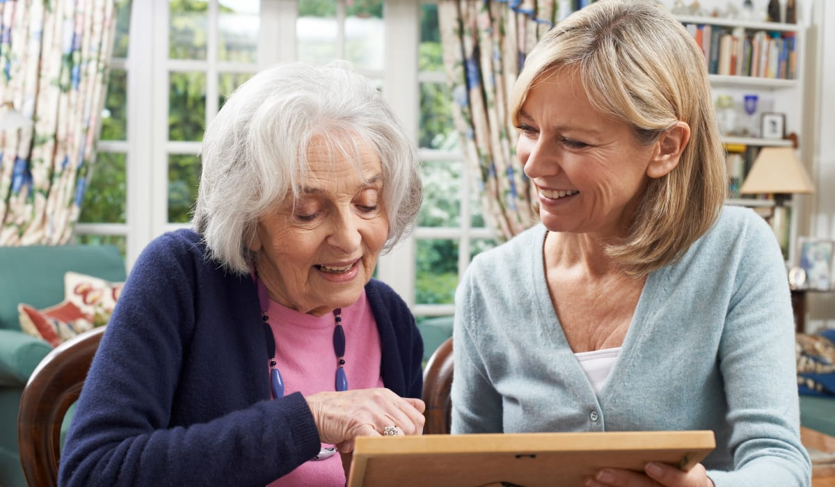 A resident and her daughter looking at a photograph at CERTUS Premier Memory Care Living in Orlando, Florida.