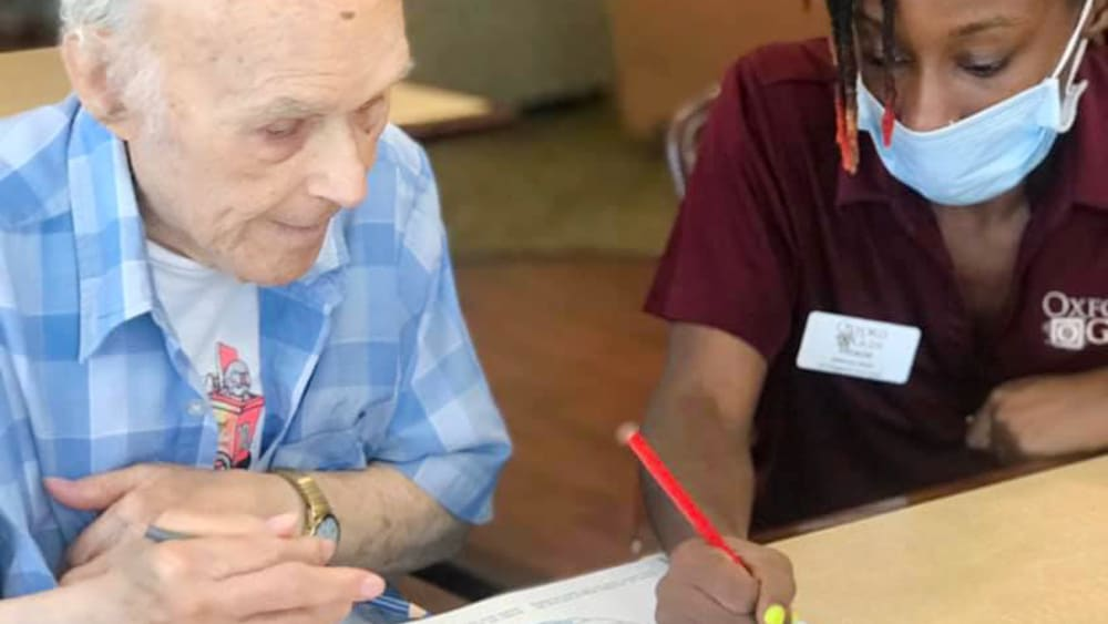 Caretaker drawing with a resident at Oxford Glen Memory Care at Carrollton in Carrollton, Texas