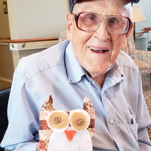 A resident holding a craftwork owl at Canoe Brook Assisted Living & Memory Care in Catoosa, Oklahoma
