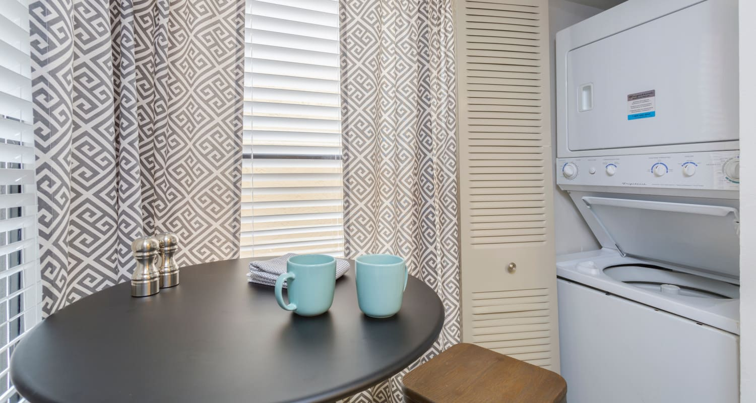 Small dining table next to washer and dryer at Siena Apartments in Plantation, Florida