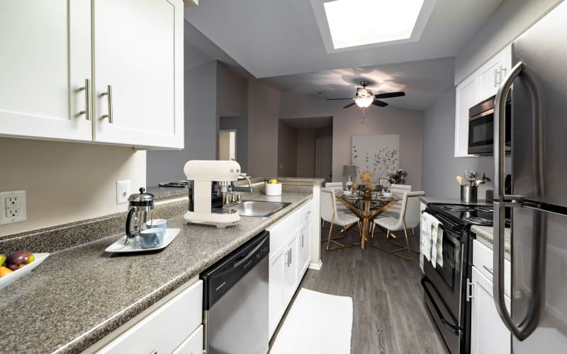 Ample counter space in a kitchen overlooking a dining room at Sierra Del Oro Apartments in Corona, California